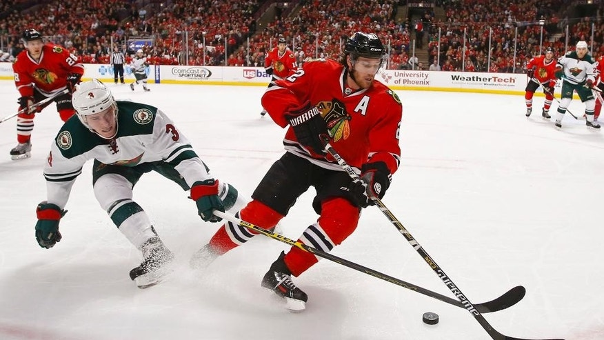 Chicago Blackhawks defenseman Duncan Keith (2) battles for the puck with Minnesota Wild center Charlie Coyle (3) during the first period of an NHL hockey game in Chicago, Sunday, Jan. 11, 2015. (AP Photo/Kamil Krzaczynski)