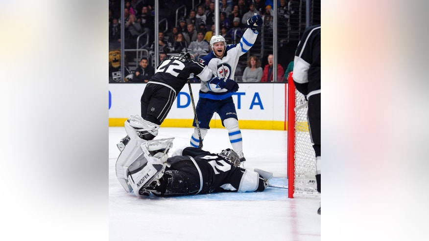Winnipeg Jets center Bryan Little, upper right, celebrates a goal by right wing Blake Wheeler  as Los Angeles Kings center Trevor Lewis defends and goalie Jonathan Quick lays on the ice during the first period of an NHL hockey game, Saturday, Jan. 10, 2015, in Los Angeles.  (AP Photo/Mark J. Terrill)