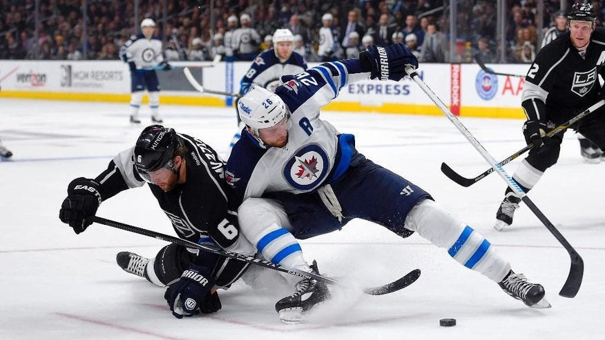 Los Angeles Kings defenseman Jake Muzzin, left, and Winnipeg Jets right wing Blake Wheeler battle for the puck during the first period of an NHL hockey game, Saturday, Jan. 10, 2015, in Los Angeles. Los Angeles Kings defenseman Matt Greene is at right. (AP Photo/Mark J. Terrill)