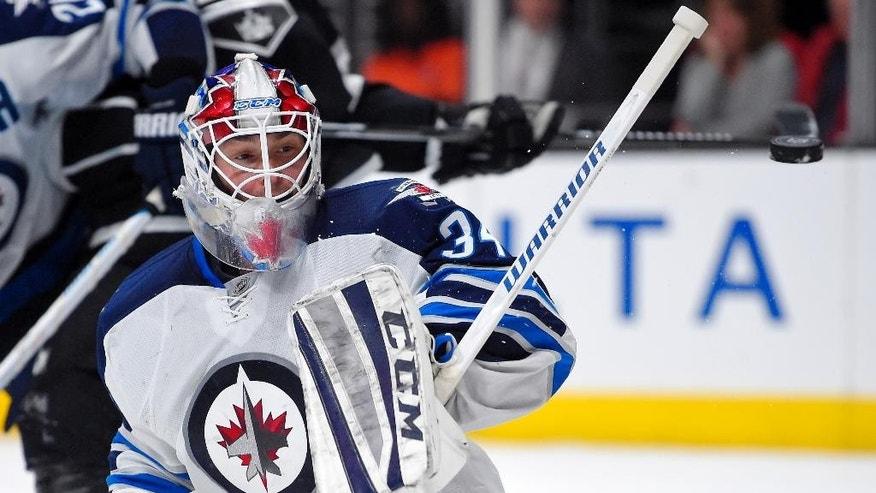 Winnipeg Jets goalie Michael Hutchinson deflects a shot during the second period of an NHL hockey game against the Los Angeles Kings, Saturday, Jan. 10, 2015, in Los Angeles.  (AP Photo/Mark J. Terrill)