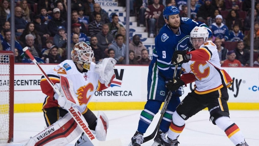 Calgary Flames defenseman Raphael Diaz (33) tries to clear Vancouver Canucks right wing Zack Kassian (9) from in front of Flames goalie Joni Ortio (37) during the first period of an NHL hockey game Saturday, Jan. 10, 2015, in Vancouver, British Columbia. (AP Photo/The Canadian Press, Jonathan Hayward)