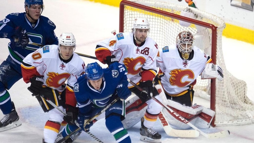 Calgary Flames center Markus Granlund (60) and teammate Kris Russell (4) try to clear Vancouver Canucks right wing Derek Dorsett (51) and center Bo Horvat (53) from in front of Flames goalie Joni Ortio (37) during the second period of an NHL hockey game Saturday, Jan. 10, 2015, in Vancouver, British Columbia. (AP Photo/The Canadian Press, Jonathan Hayward)