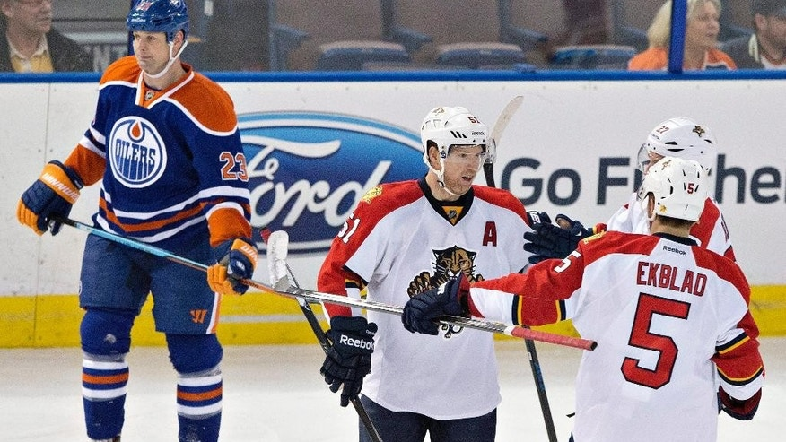 Florida Panthers Brian Campbell (51), Nick Bjugstad (27) and Aaron Ekblad (5) celebrate a goal as Edmonton Oilers Matt Hendricks (23) skates past during first period NHL hockey action in Edmonton, Alberta, Sunday, Jan. 11, 2015. (AP Photo/The Canadian Press, Jason Franson)