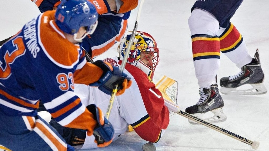 Florida Panthers goalie Roberto Luongo (1) makes a save as Edmonton Oilers Ryan Nugent-Hopkins (93) looks for the rebound during first period NHL hockey action in Edmonton, Alberta, Sunday, Jan. 11, 2015. (AP Photo/The Canadian Press, Jason Franson)