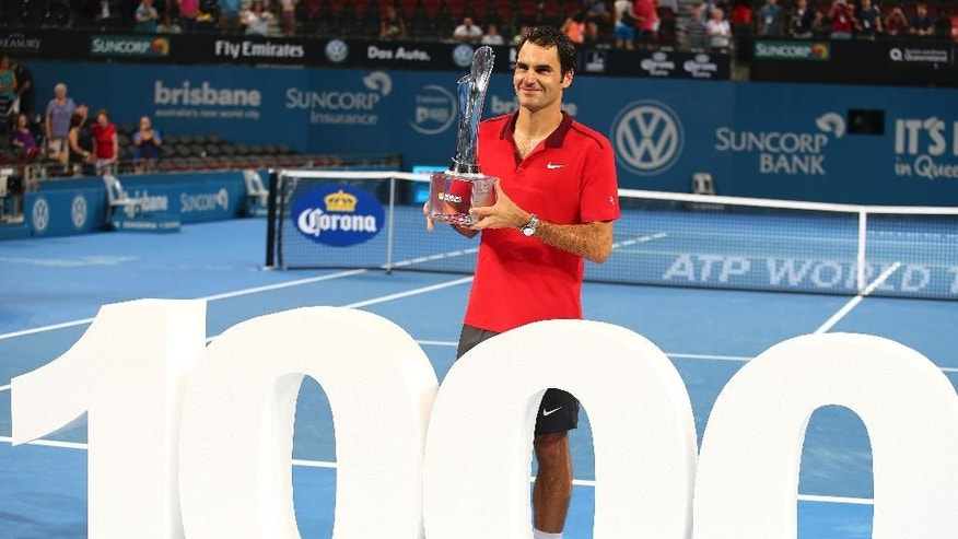 Roger Federer of Switzerland holds the winner's trophy and pose for photos after he won his 1000th career title in the men's final match against Milos Raonic of Canada during the Brisbane International tennis tournament in Brisbane, Australia, Sunday, Jan. 11, 2015. Federer notched his 1,000th career victory and collected his 83rd title with a seesawing 6-4, 6-7 (2), 6-4 win over third-seeded Milos Raonic of Canada in the Brisbane International final on Sunday. (AP Photo/Tertius Pickard)