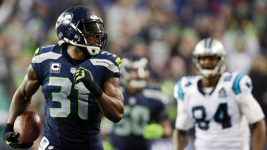 Jan. 10, 2015: Seattle Seahawks strong safety Kam Chancellor (31) runs in front of Carolina Panthers tight end Ed Dickson (84) to score on an interception 90 yards for a touchdown during the second half of an NFL divisional playoff football game in Seattle