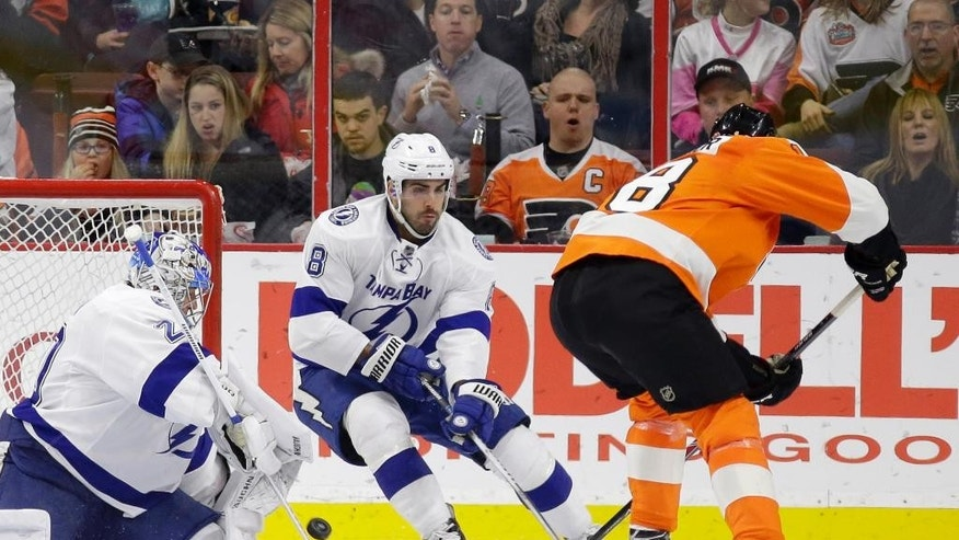 Philadelphia Flyers' R.J. Umberger, right, scores a goal against Tampa Bay Lightning's Evgeni Nabokov, left, of Kazakhstan, and Mark Barberio during the first period of an NHL hockey game, Monday, Jan. 12, 2015, in Philadelphia. (AP Photo/Matt Slocum)