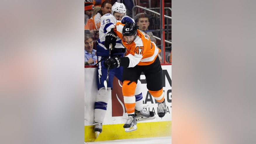 Philadelphia Flyers' Andrew MacDonald (47) and Tampa Bay Lightning's Cedric Paquette (13) collide during the first period of an NHL hockey game, Monday, Jan. 12, 2015, in Philadelphia. (AP Photo/Matt Slocum)