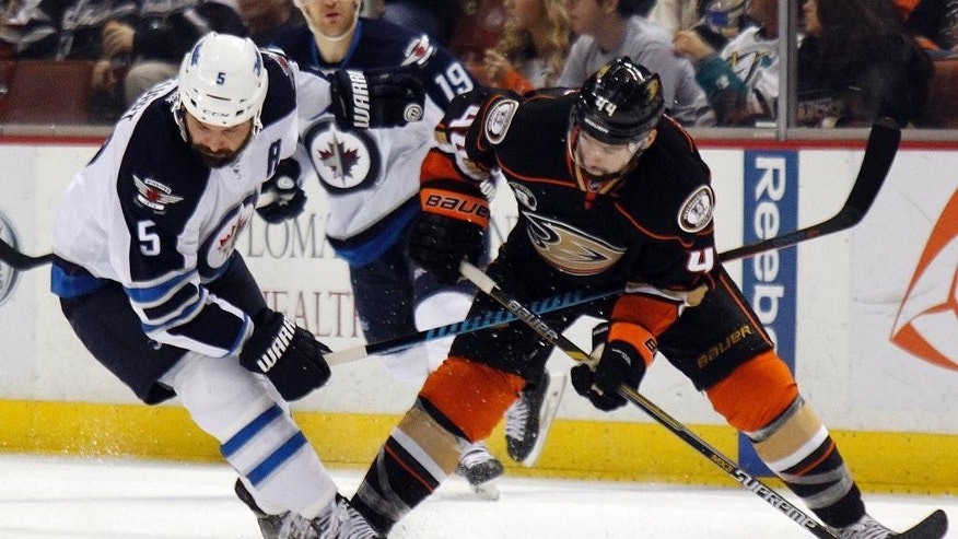 Winnipeg Jets defenseman Mark Stuart, left, shields Anaheim Ducks center Nate Thompson (44) from the puck during the second period of an NHL hockey game in Anaheim, Calif., Sunday, Jan. 11, 2015. (AP Photo/Alex Gallardo)