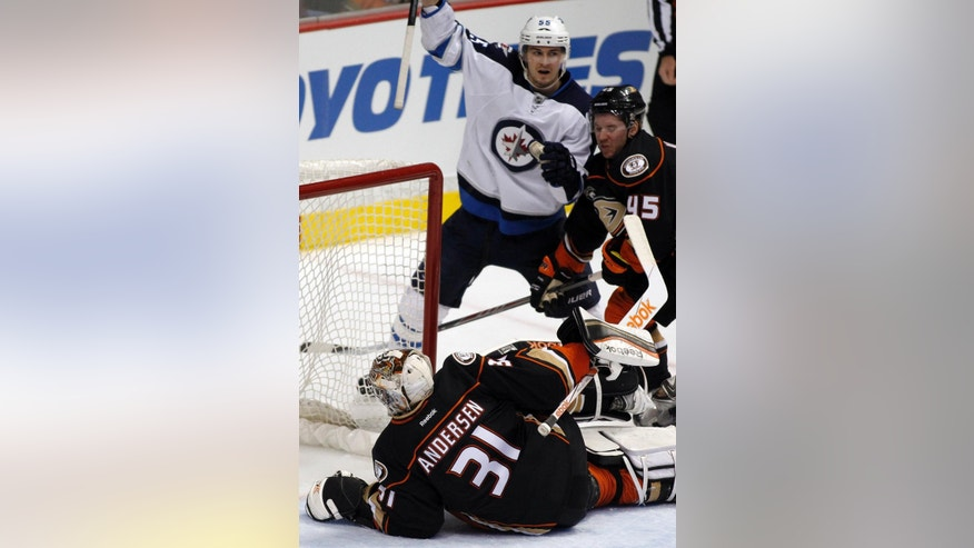 Winnipeg Jets center Mark Scheifele, center, reacts after he scores against Anaheim Ducks goalie Frederik Andersen (31), of Denmark, and defenseman Sami Vatanen (45), of Finland, during the first period of an NHL hockey game in Anaheim, Calif., Sunday, Jan. 11, 2015. (AP Photo/Alex Gallardo)