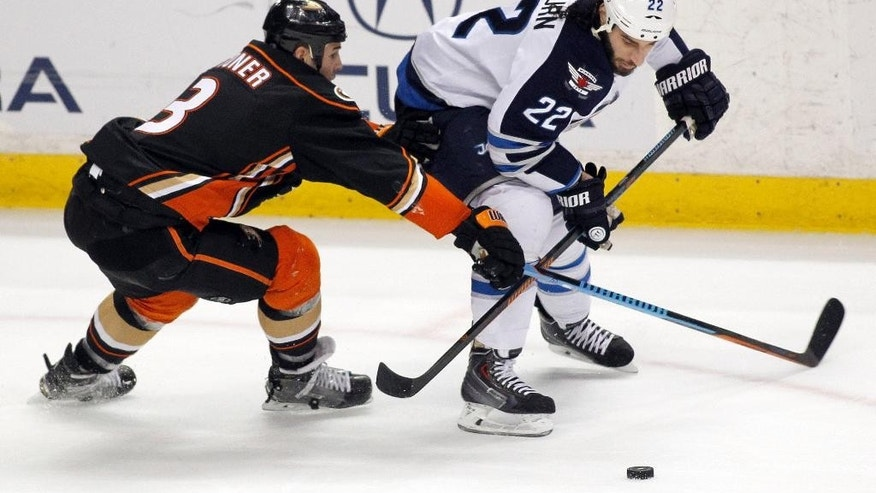 Anaheim Ducks defenseman Clayton Stoner (3) battles Winnipeg Jets right wing Chris Thorburn (22) for the puck during the first period of an NHL hockey game in Anaheim, Calif., Sunday, Jan. 11, 2015. (AP Photo/Alex Gallardo)