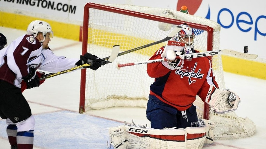 Washington Capitals goalie Braden Holtby (70) reaches for the puck against Colorado Avalanche center John Mitchell (7) during the third period of an NHL hockey game, Monday, Jan. 12, 2015, in Washington. The Capitals won 2-1. (AP Photo/Nick Wass)