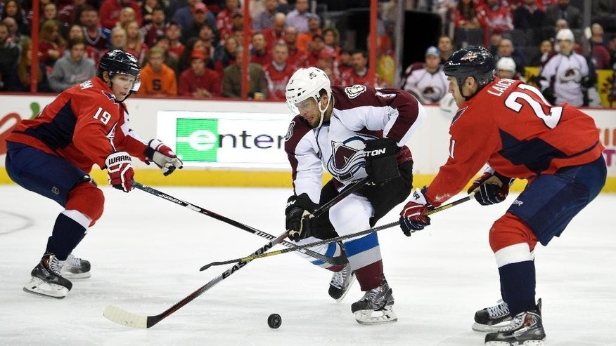 Washington Capitals center Brooks Laich (21) and Nicklas Backstrom (19), of Sweden, battle for the puck against Colorado Avalanche defenseman Nate Guenin, center, during the second period of an NHL hockey game, Monday, Jan. 12, 2015, in Washington. (AP Photo/Nick Wass)