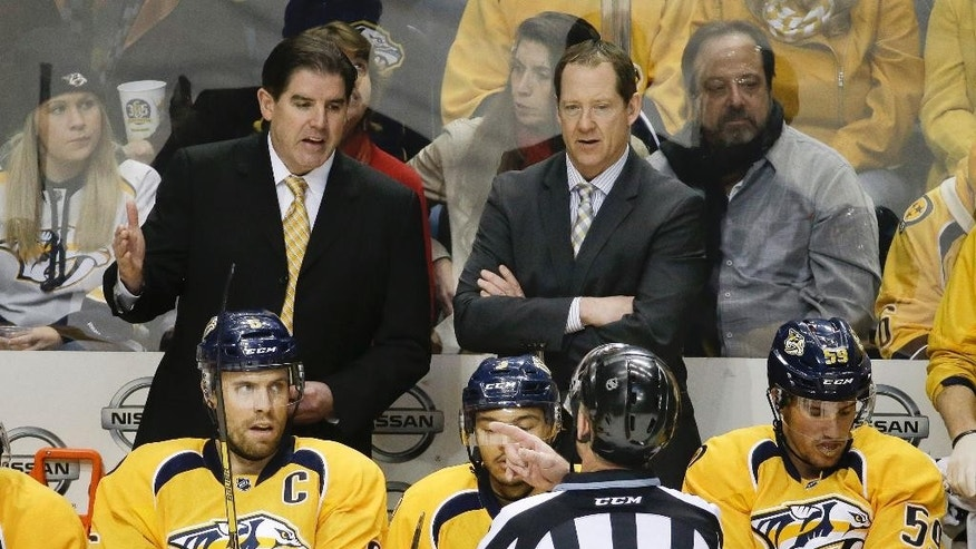 Nashville Predators head coach Peter Laviolette, top left, and assistant coach Phil Housley listen to linesman Brad Lazarowich (86) in the second period of an NHL hockey game against the Vancouver Canucks Tuesday, Jan. 13, 2015, in Nashville, Tenn. (AP Photo/Mark Humphrey)