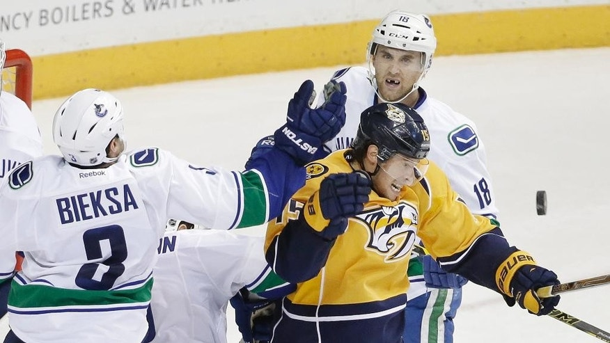 Nashville Predators center Craig Smith (15) reaches for the puck with Vancouver Canucks defenseman Kevin Bieksa (3) in the second period of an NHL hockey game Tuesday, Jan. 13, 2015, in Nashville, Tenn. Behind Smith is Vancouver Canucks defenseman Ryan Stanton (18). (AP Photo/Mark Humphrey)