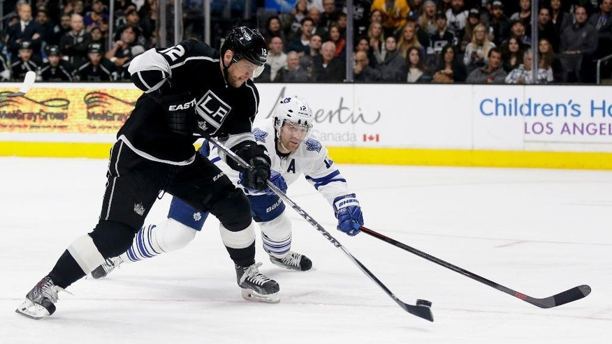 Los Angeles Kings right wing Marian Gaborik, left, shoots past Toronto Maple Leafs defenseman Stephane Robidas during the second period of an NHL hockey game in Los Angeles, Monday, Jan. 12, 2015. (AP Photo/Chris Carlson)