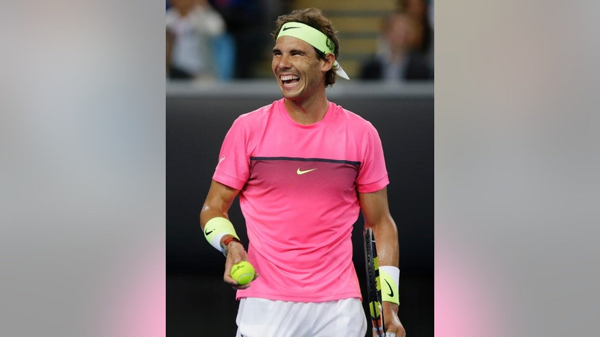 Spain's Rafael Nadal jokes with a spectator during an exhibition match against Australia's Mark Philippoussis on Margaret Court Arena ahead of the Australian Open tennis championship in Melbourne, Australia, Wednesday, Jan. 14, 2015. The opening Grand Slam event of the year begins here on Monday January 19.  (AP Photo/Mark Baker)