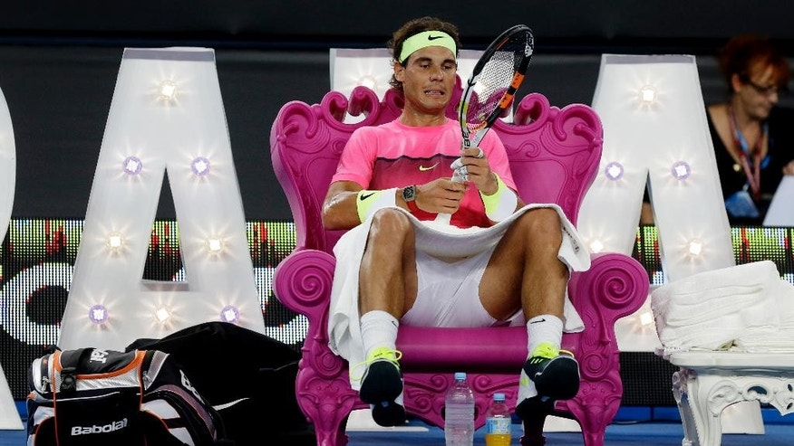 Spain's Rafael Nadal takes a rest in a court side chair during a break in his exhibition match against Australia's Mark Philippoussis on Margaret Court Arena ahead of the Australian Open tennis championship in Melbourne, Australia, Wednesday, Jan. 14, 2015. The opening Grand Slam event of the year begins here on Monday January 19.  (AP Photo/Mark Baker)
