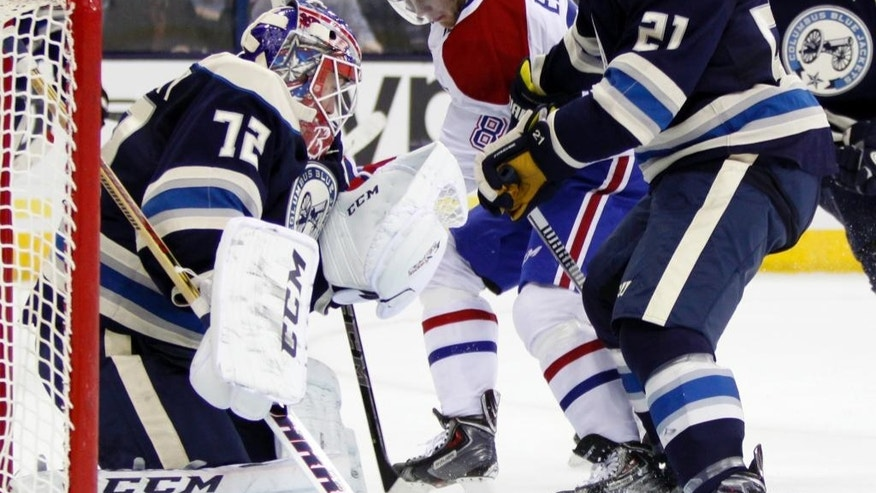 Columbus Blue Jackets goalie Sergei Bobrovosky (72), of Russia, stops a shot from Montreal Canadiens' Lars Eller (81), of Denmark, as Blue Jackets' James Wisniewski (21) looks on during the first period of an NHL hockey game in Columbus, Ohio, Wednesday, Jan. 14, 2015. (AP Photo/Paul Vernon)