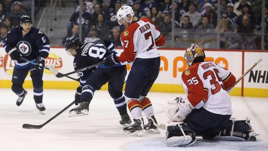 Winnipeg Jets' Mathieu Perreault (85) tips a shot past Florida Panthers' Dmitry Kulikov (7) and between the legs of goaltender Al Montoya (35) to complete a hat trick during the second period of an NHL hockey game Tuesday, Jan. 13, 2015, in Winnipeg, Manitoba. (AP Photo/The Canadian Press, Trevor Hagan)