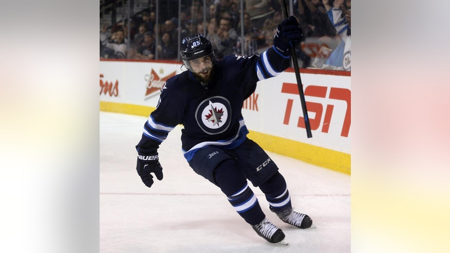 Winnipeg Jets' Mathieu Perreault (85) celebrates his fourth goal of the night against the Florida Panthers, during the second period of an NHL hockey game Tuesday, Jan. 13, 2015, in Winnipeg, Manitoba. (AP Photo/The Canadian Press, Trevor Hagan)
