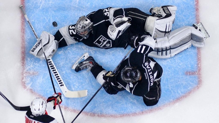 Los Angeles Kings goalie Jonathan Quick, top, is scored on by New Jersey Devils left wing Mike Cammalleri, lower left, as center Anze Kopitar, of Slovenia, defends during the second period of an NHL hockey game, Wednesday, Jan. 14, 2015, in Los Angeles. (AP Photo/Mark J. Terrill)
