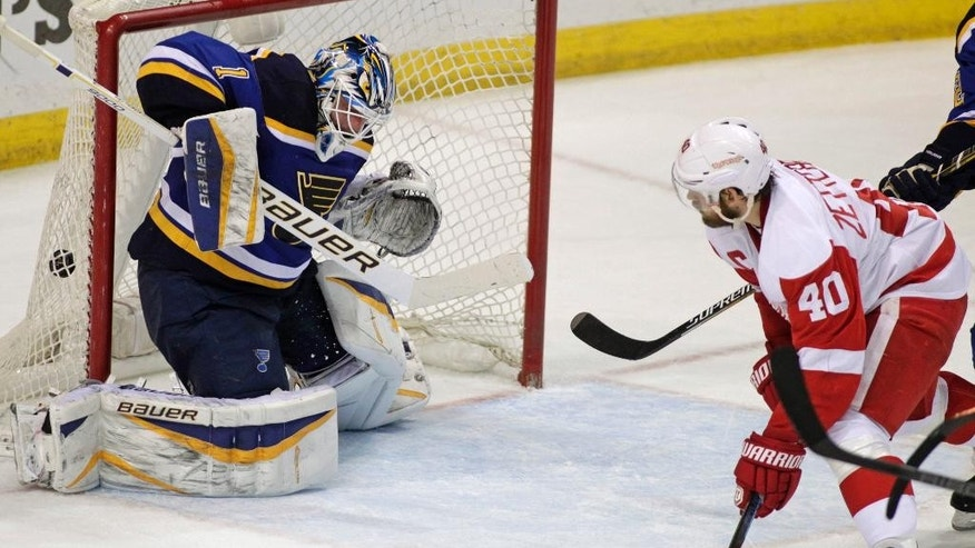 Detroit Red Wings' Henrik Zetterberg (40) watches a shot from teammate Pavel Datsyuk get past St. Louis Blues goalie Brian Elliott (1) for the win with 2.2 seconds left in overtime of an NHL hockey game, Thursday, Jan. 15, 2015, in St. Louis. The Red Wings won 3-2. (AP Photo/Tom Gannam)