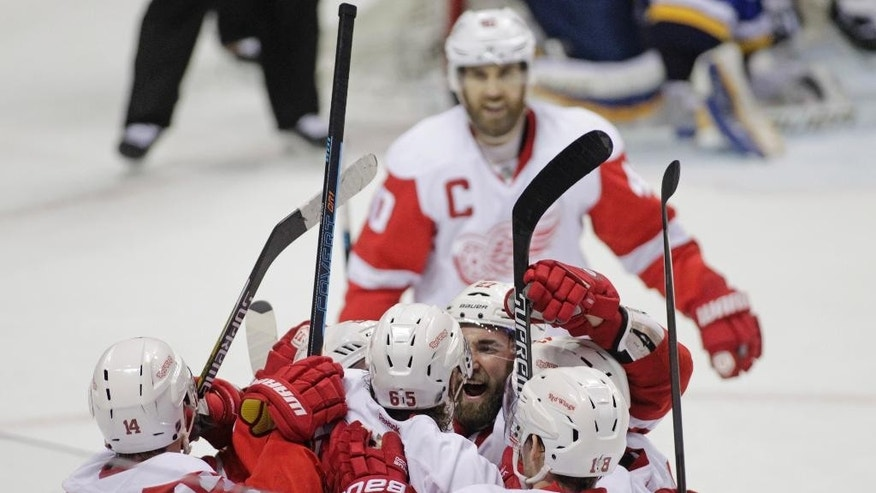 Detroit Red Wings' Kyle Quincey (27) celebrates with teammates Gustav Nyquist (14), Danny DeKeyser (65) snf Joakim Andersson (18) after the Red Wings defeated the St. Louis Blues in overtime in an NHL hockey game, Thursday, Jan. 15, 2015, in St. Louis. The Red Wings won 3-2. (AP Photo/Tom Gannam)