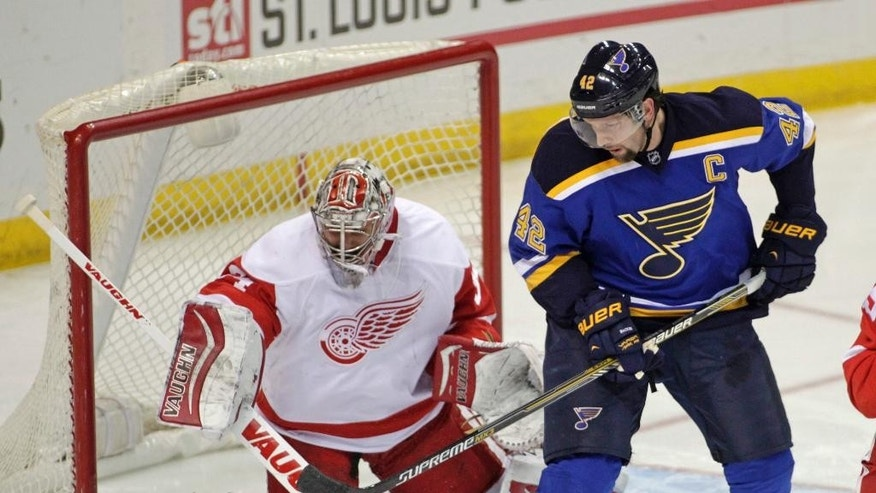 St. Louis Blues' David Backes (42) redirects the puck past Detroit Red Wings goalie Petr Mrazek (34) for a goal during the third period of an NHL hockey game, Thursday, Jan. 15, 2015, in St. Louis. The Red Wings won 3-2 in overtime. (AP Photo/Tom Gannam)