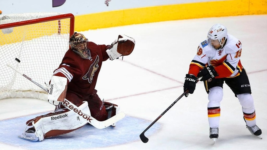 Arizona Coyotes' Mike Smith, left, gives up a goal to Calgary Flames' Mark Giordano, not seen, as Flames' David Jones (19) creates a screen in front of the net during the third period of an NHL hockey game Thursday, Jan. 15, 2015, in Glendale, Ariz.  The Flames defeated the Coyotes 4-1. (AP Photo/Ross D. Franklin)