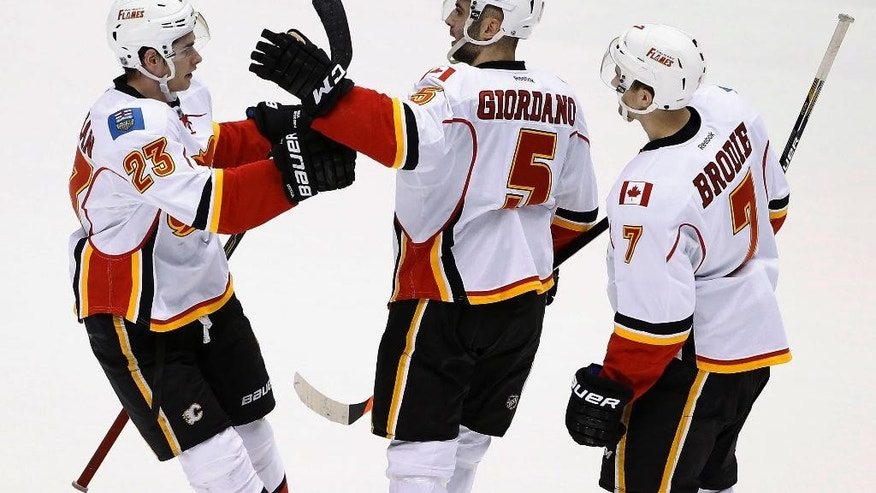 Calgary Flames' Mark Giordano (5) celebrates his goal against the Arizona Coyotes with teammates Sean Monahan (23) and T.J. Brodie (7) during the third period of an NHL hockey game Thursday, Jan. 15, 2015, in Glendale, Ariz. The Flames defeated the Coyotes 4-1. (AP Photo/Ross D. Franklin)