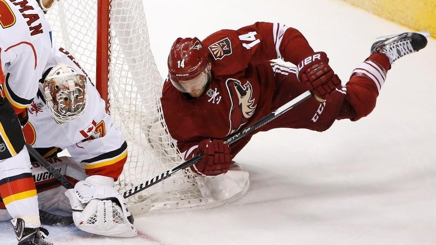 Calgary Flames' Joni Ortio, second from left, of Finland, makes a save on a shot by Arizona Coyotes' Joe Vitale (14) as Flames' Dennis Wideman (6) defends during the first period of an NHL hockey game Thursday, Jan. 15, 2015, in Glendale, Ariz. (AP Photo/Ross D. Franklin)