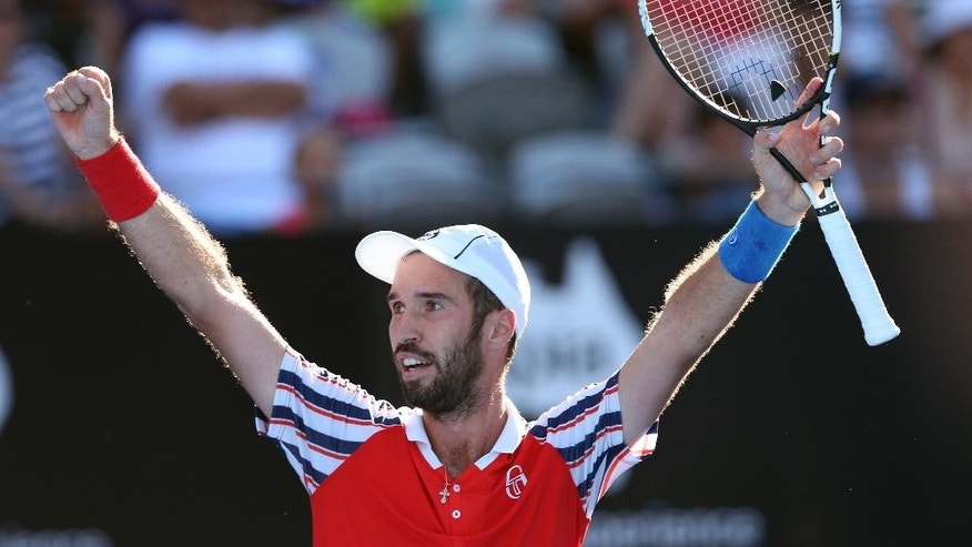 Mikhail Kukushkin of Kazakhstan raises his arms as he celebrates winning his match against Juan Martin del Potro of Argentina at the Sydney International Tennis tournament in Sydney, Australia, Thursday, Jan. 15, 2015. (AP Photo/Rob Griffith)