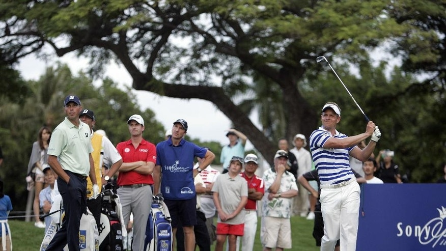 Luke Donald, right, from England, follows his ball after teeing off on the 11th hole as Matt Kuchar, left, and Webb Simpson (wearing red shirt) watch during the first round of the Sony Open golf tournament, Thursday, Jan, 15, 2015, in Honolulu, Hawaii. (AP Photo/Hugh Gentry)