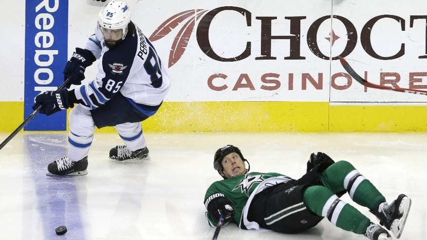 Dallas Stars center Cody Eakin (20) falls to the ice as Winnipeg Jets center Mathieu Perreault (85) skates past during the third period of an NHL hockey game Thursday, Jan. 15, 2015, in Dallas. The Jets won 2-1. (AP Photo/LM Otero)