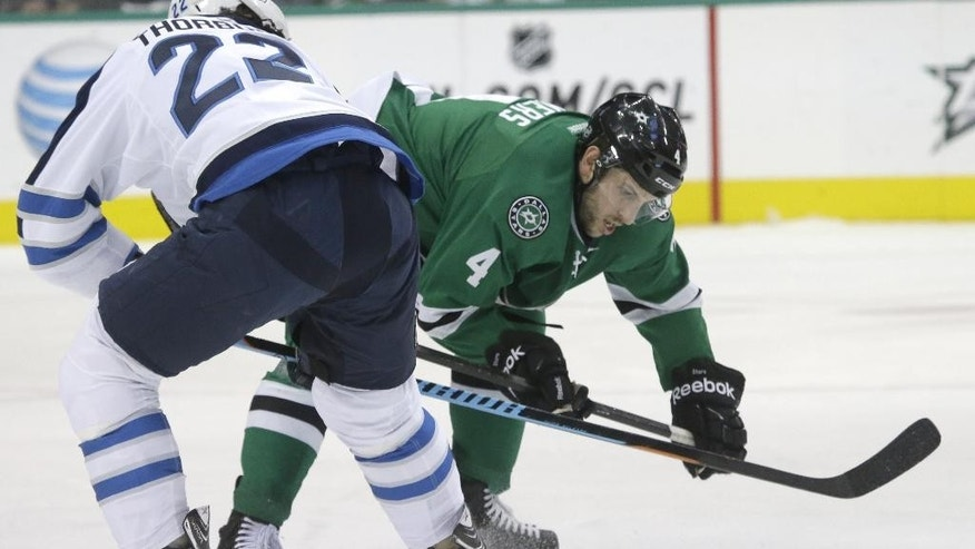 Dallas Stars defenseman Jason Demers (4) and Winnipeg Jets defenseman Jay Harrison (23) fight for control of the puck during the first period of an NHL hockey game Thursday, Jan. 15, 2015, in Dallas. (AP Photo/LM Otero)