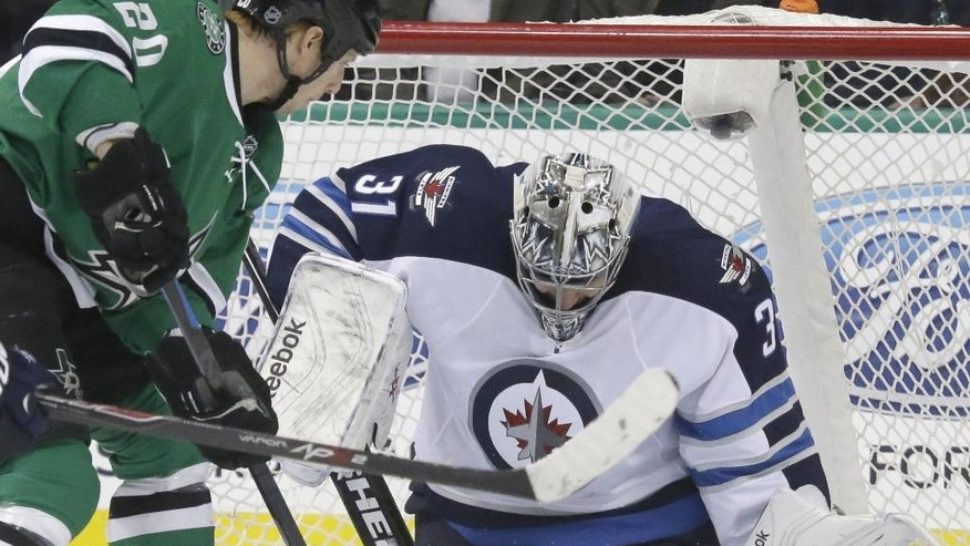 Winnipeg Jets goalie Ondrej Pavelec (31) blocks a shot against Dallas Stars center Cody Eakin (20) during the first period of an NHL hockey game Thursday, Jan. 15, 2015, in Dallas. (AP Photo/LM Otero)