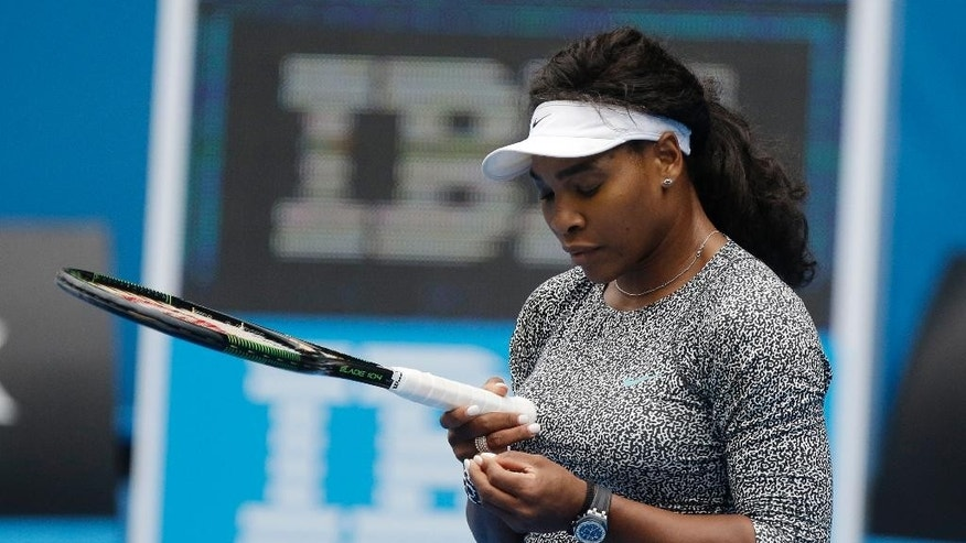 Serena Williams of the US looks at her racket during a practice session on Rod Laver Arena ahead of the Australian Open tennis championship in Melbourne, Australia, Thursday, Jan. 15, 2015. (AP Photo/Mark Baker)