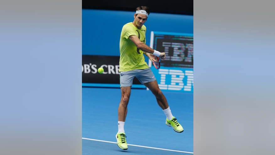 Switzerland's Roger Federer makes a backhand return during a practice session on Rod Laver Arena ahead of the Australian Open tennis championship in Melbourne, Australia, Thursday, Jan. 15, 2015. (AP Photo/Mark Baker)