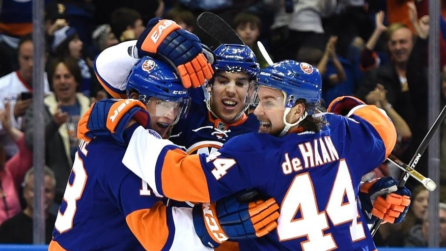 New York Islanders center Ryan Strome, left, celebrates his goal with defenseman Travis Hamonic, center, and defenseman Calvin de Haan (44) during the second period of an NHL hockey game against the Pittsburgh Penguins at Nassau Coliseum on Friday, Jan. 16, 2015, in Uniondale, N.Y. (AP Photo/Kathy Kmonicek)