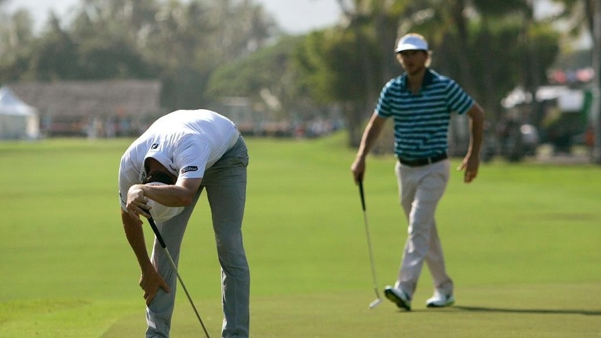 Jimmy Walker reacts to missing a putt on the 10th green as Russell Henley walks behind him during the first round of the Sony Open golf tournament, Thursday, Jan, 15, 2015, in Honolulu. (AP Photo/Hugh Gentry)
