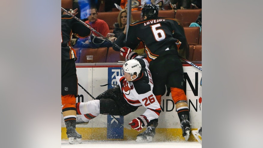 New Jersey Devils'  Patrik Elias (26) gets the worst of a collision with Anaheim Ducks' Ben Lovejoy (6) during the first period of an NHL hockey game, Friday, Jan. 16, 2015, in Anaheim, Calif. (AP Photo/Christine Cotter)
