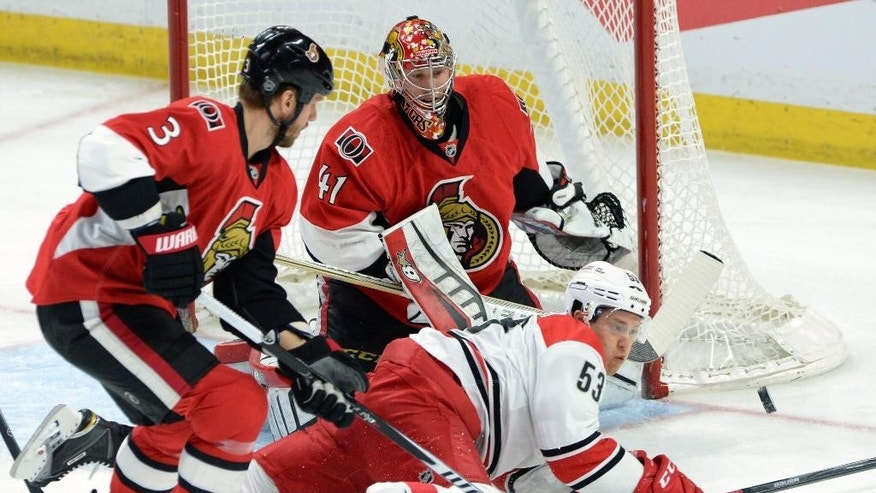 Ottawa Senators' Craig Anderson minds the net as Carolina Hurricanes' Jeff Skinner (53) keeps his eye on the puck as he falls to the ice as Senators' Marc Methot (3) defends during the first period on an NHL hockey game, Saturday, Jan. 17, 2015 in Ottawa, Ontario. (AP Photo/Canadian Press, Sean Kilpatrick)