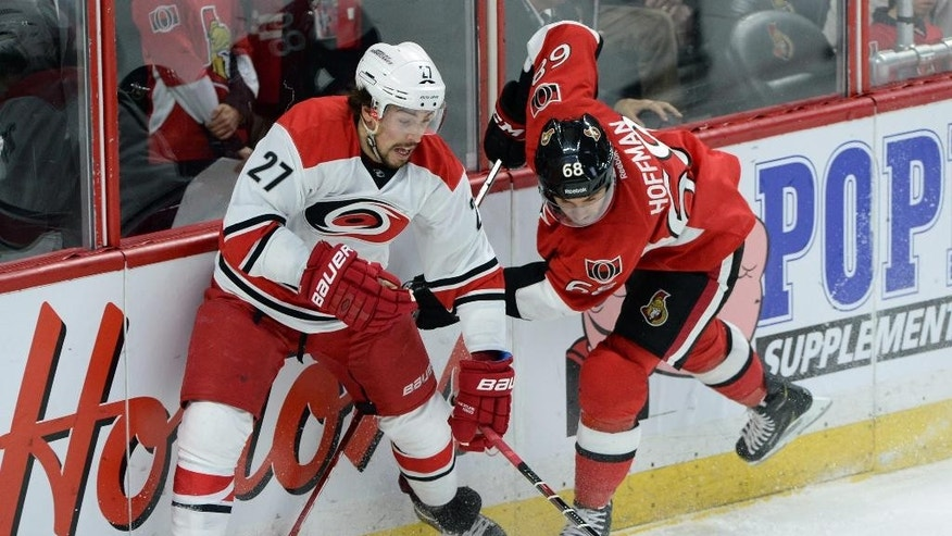 Carolina Hurricanes' Justin Faulk keeps the puck from Ottawa Senators' Mike Hoffman during the first period on an NHL hockey game, Saturday, Jan. 17, 2015 in Ottawa, Ontario. (AP Photo/Canadian Press, Sean Kilpatrick)