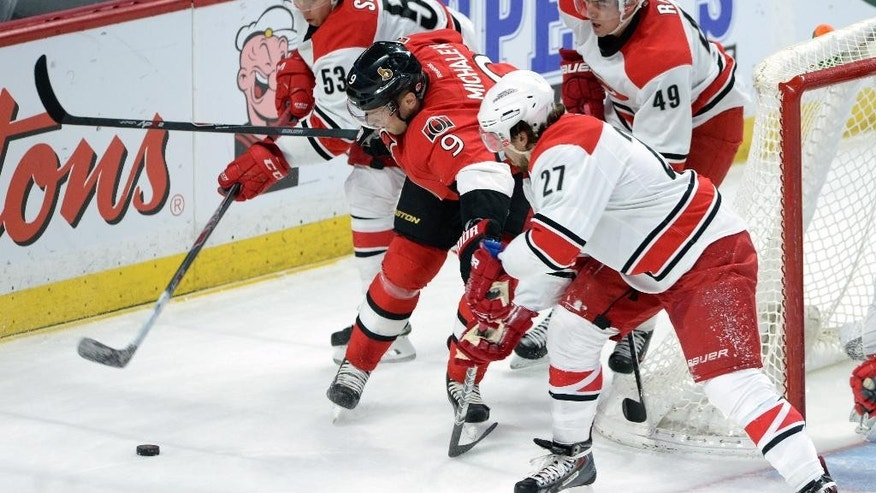 Ottawa Senators' Milan Michalek, (9) tries to hold off Carolina Hurricanes' Jeff Skinner (53) Victor Rask (49) and Justin Faulk (27) during the first period on an NHL hockey game, Saturday, Jan. 17, 2015 in Ottawa, Ontario. (AP Photo/Canadian Press, Sean Kilpatrick)