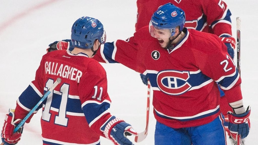 Montreal Canadiens' Alex Galchenyuk, right, celebrates with teammate Brendan Gallagher after scoring against the New York Islanders during third-period NHL hockey game action in Montreal, Saturday, Jan. 17, 2015. (AP Photo/The Canadian Press, Graham Hughes)