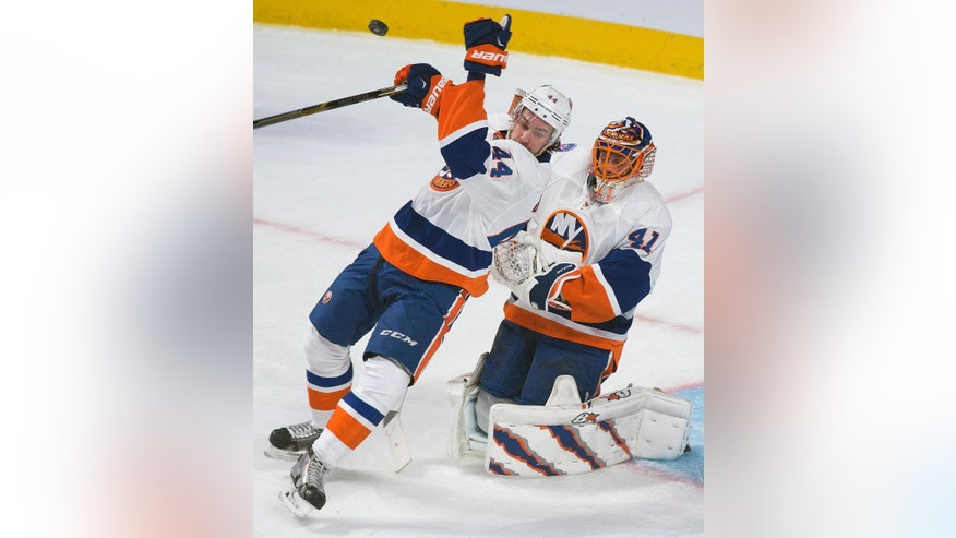 New York Islanders goaltender Jaroslav Halak, right, collides with teammate Calvin de Haan during second-period NHL hockey game action against the Montreal Canadiens in Montreal, Saturday, Jan. 17, 2015. (AP Photo/The Canadian Press, Graham Hughes)
