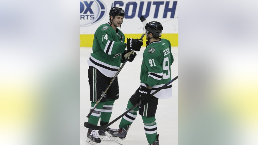 Dallas Stars left wing Jamie Benn (14) and center Tyler Seguin (91) congratulate each other at the end of the third period of an NHL hockey game against the Washington Capitals on Saturday, Jan. 17, 2015, in Dallas. The Stars won 5-4. (AP Photo/LM Otero)