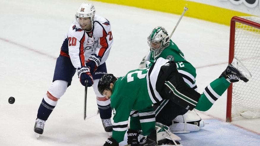 Washington Capitals right wing Troy Brouwer (20) tries to shoot as Dallas Stars defenseman Jordie Benn (24) and goalie Kari Lehtonen (32) defend the goal during the third period of an NHL hockey game Saturday, Jan. 17, 2015, in Dallas. The Stars won 5-4. (AP Photo/LM Otero)