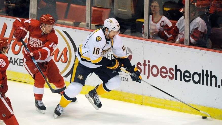 Nashville Predators left wing James Neal (18) keeps the puck away from Detroit Red Wings center Gustav Nyquist (14) during the first period of an NHL hockey game in Detroit, Saturday, Jan. 17, 2015.  (AP Photo/Jose Juarez)